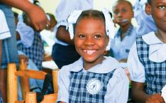 A girl wearing a school uniform sits in her classroom and smiles