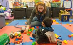 A woman and young child play together with colorful toys on a floormat