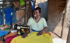 Woman smiles by sewing machine