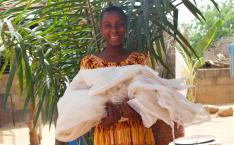 Girl smiles and holds mosquito net
