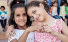 Two girls smile and make a heart shape with their hands.