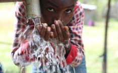 Boy looks at camera while drinking from a well.